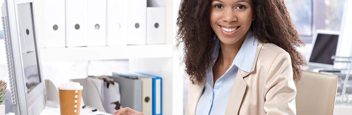 Woman sitting at computer and smiling