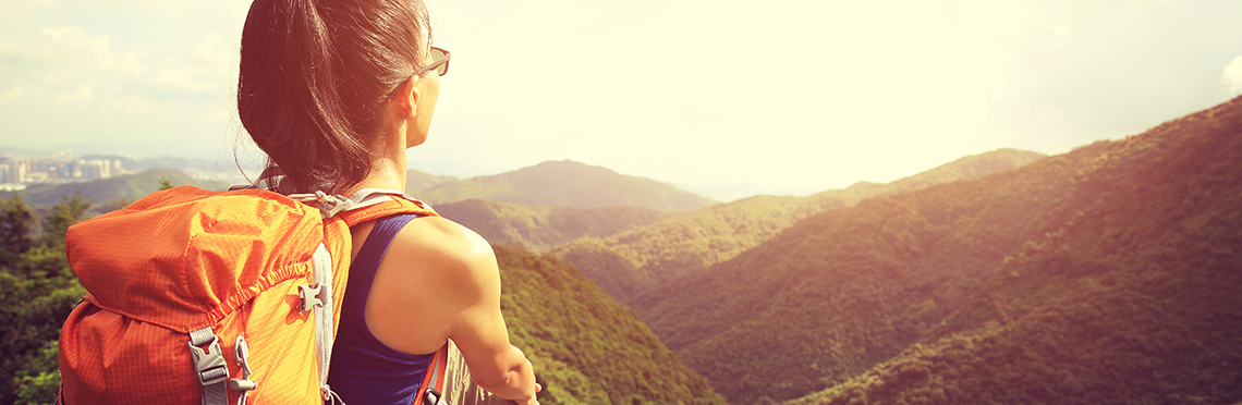 Woman with backpack sitting on rock looking out over trees and mountain range