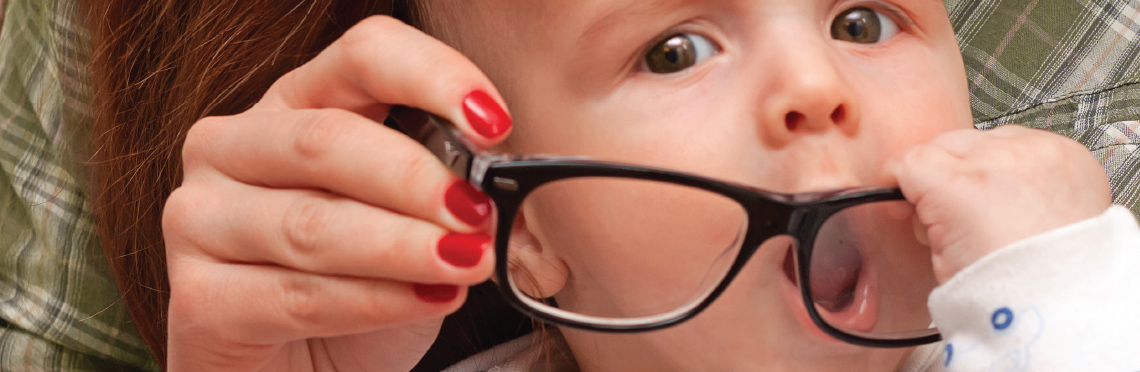 Picture of a baby with a pair of eyeglasses and trying to eat them