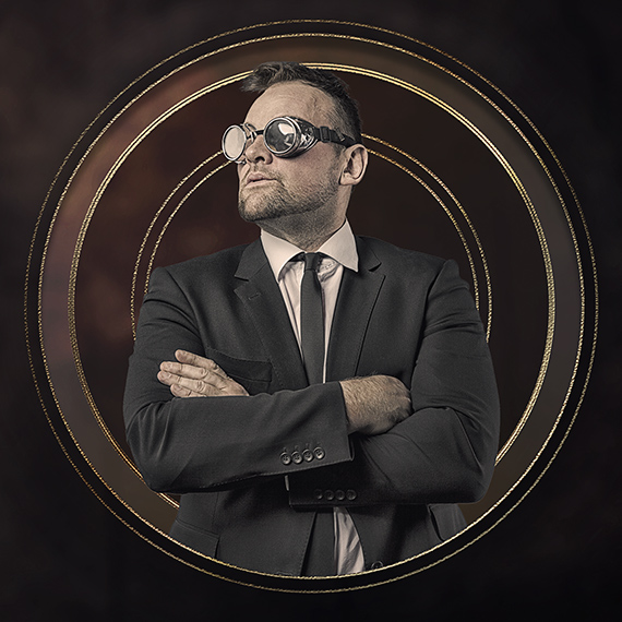 A person in a suit pretending to look steam punk by wearing goggles