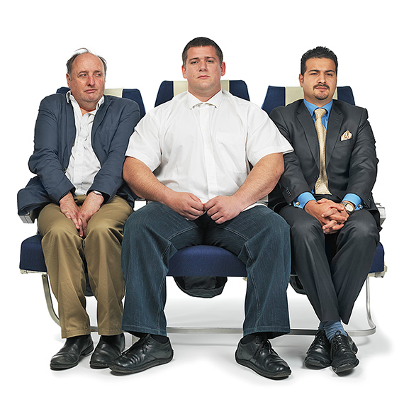 Picture of 3 people jammed into their seats in coach class on an airplane