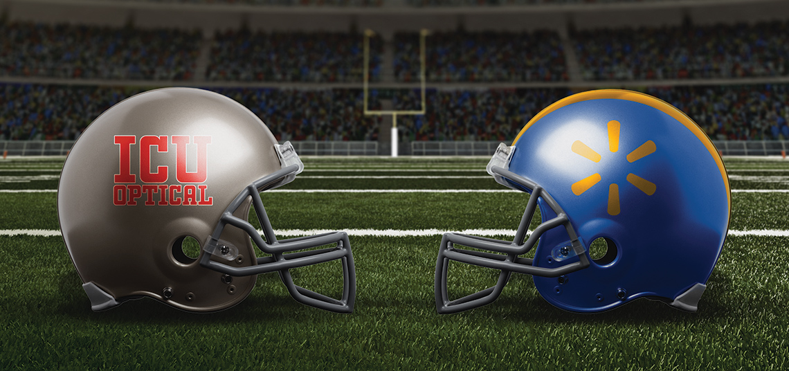 Picture of 2 football helmets. One helment has a collegiate font that says ICU Optical on the side. The other helmet has an abstract shape in yellow on a blue base.