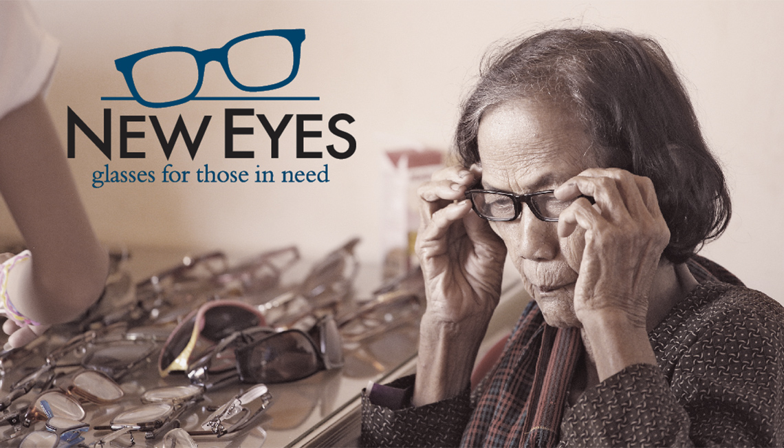 Image of elderly woman putting glasses on