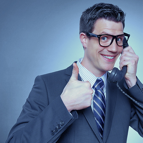 Picture of a business man on the phone with a goofy smile and giving the 'thumbs up' sign