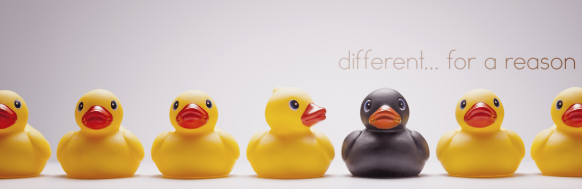 yellow rubber ducks in a row with one of the ducks colorized in black to look different
