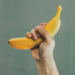 "Thumbnail image for article ""What is OPT? - The Philosophy of OPT"". A hand making a first holding a banana."