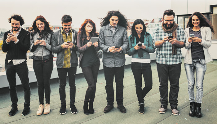"""Whippersnappers"" image for ""One Site to Rule them All"" article. Group of eight people all looking at their phones."