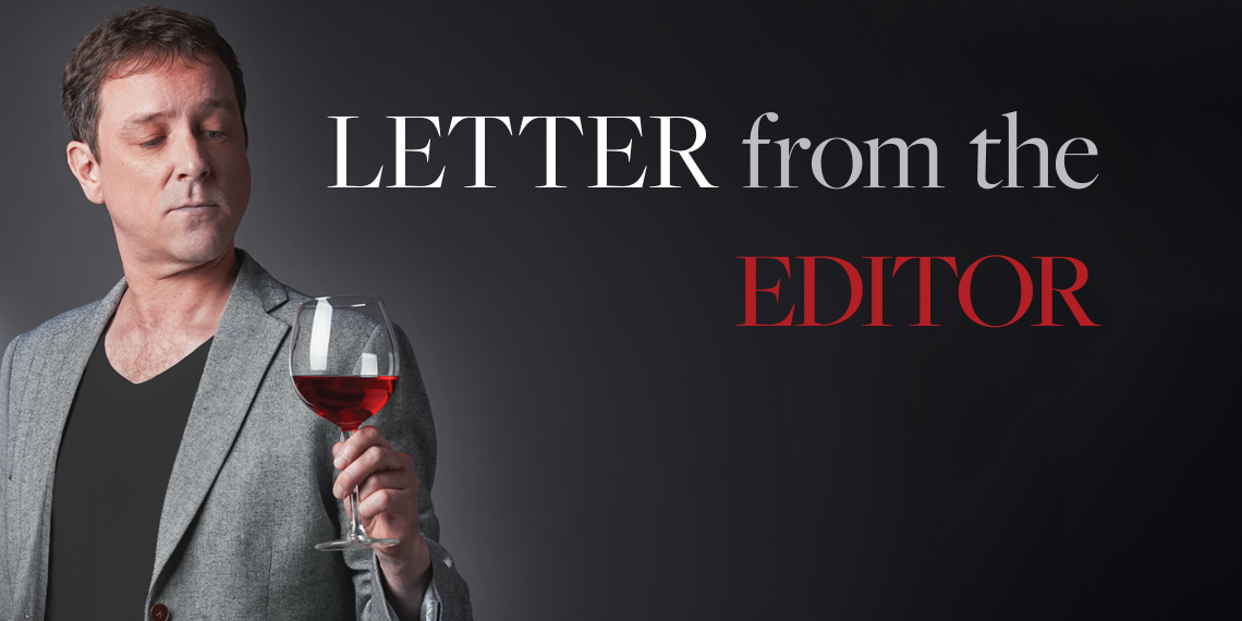 "Hero image for ""Letter from the Editor"" article. Photo of a man holding a glass of red wine."